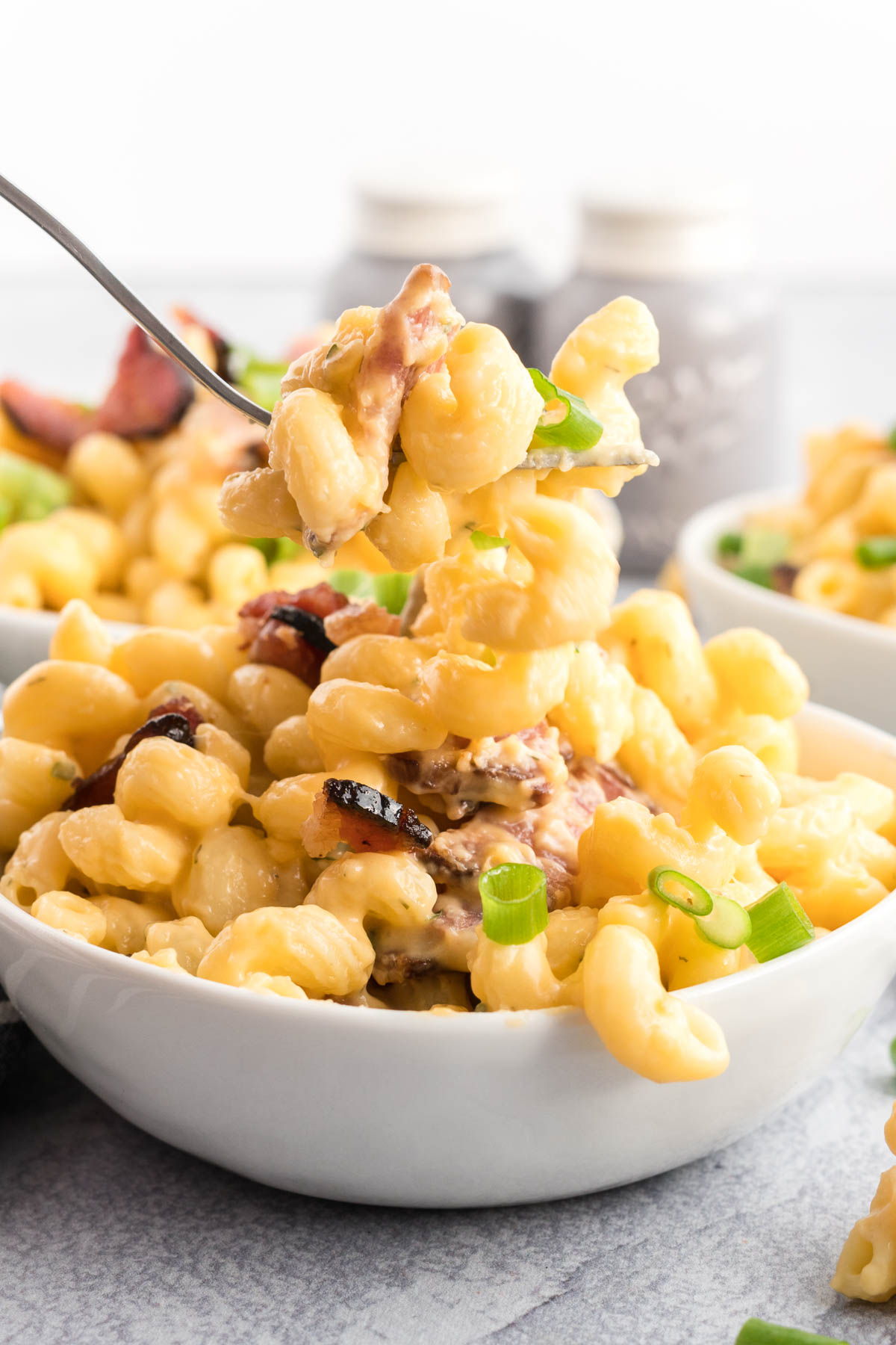 Bowl of bacon Mac and cheese with a bite on a fork.
