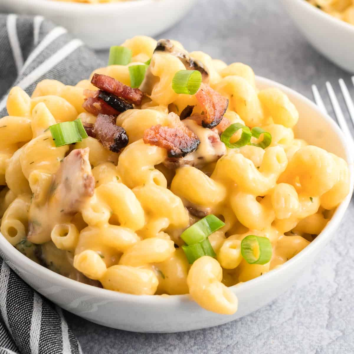 Macaroni and cheese with bacon garnished with green onion.