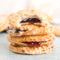 Stack of blueberry hand pies with filling oozing out.