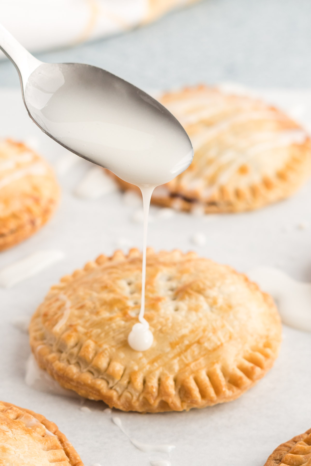 A spoon of icing being drizzled over hand pie.