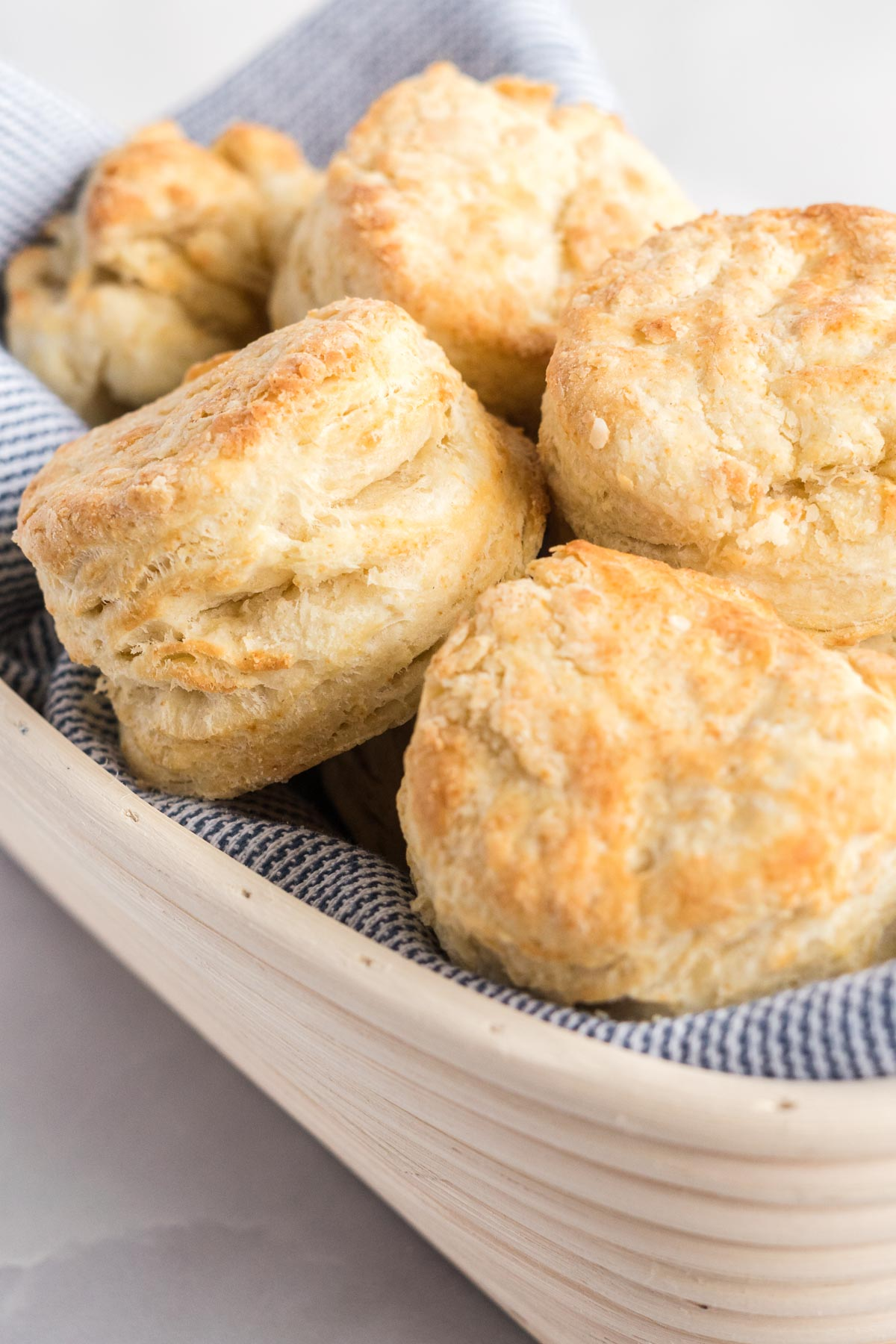 Biscuits in a basket lined with a blue towel.