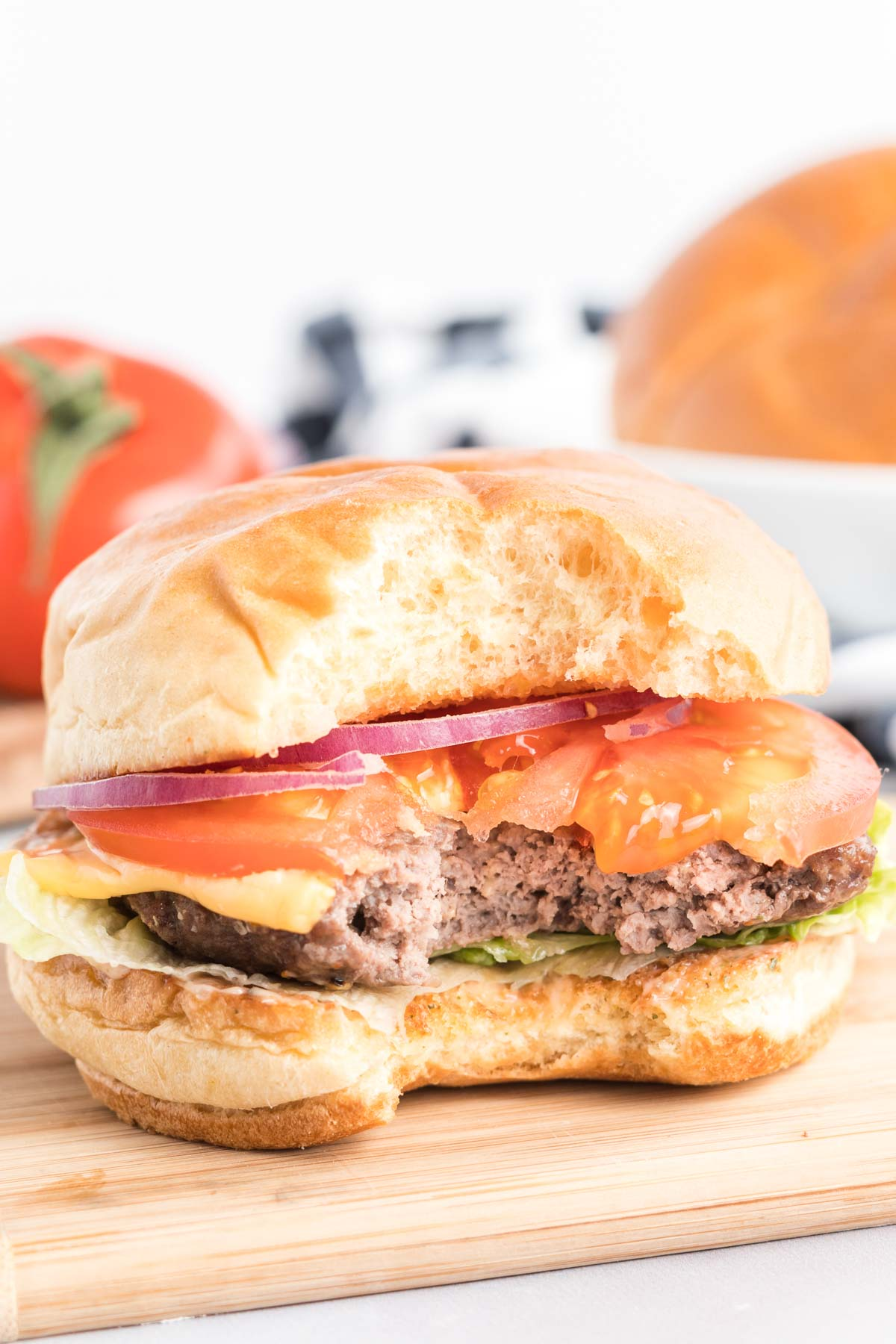 Hamburger with sauce, cheese, lettuce, tomato and onion with a bite taken out.
