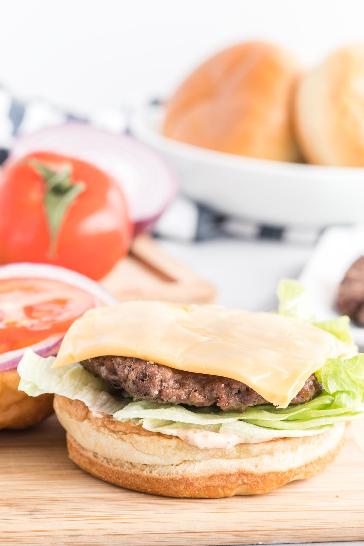 Burger patty on a bottom bun with sauce, lettuce and cheese and a tomato in the background.