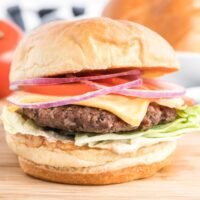 Beef burger on brioche bun topped with lettuce, tomato and onion.