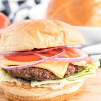 Hamburger on a wooden board topped with sauce, lettuce, cheese, tomato and red onions.