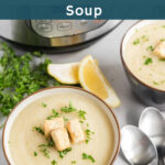 Cauliflower soup in a bowl garnished with croutons and chopped parsley with lemon wedge on the side.