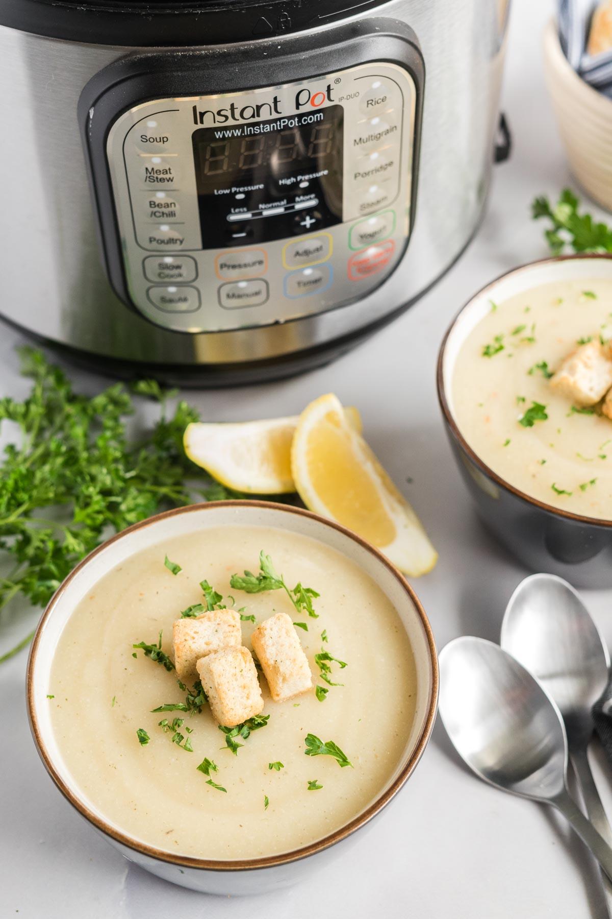 Cauliflower soup in bowls beside an instant pot.