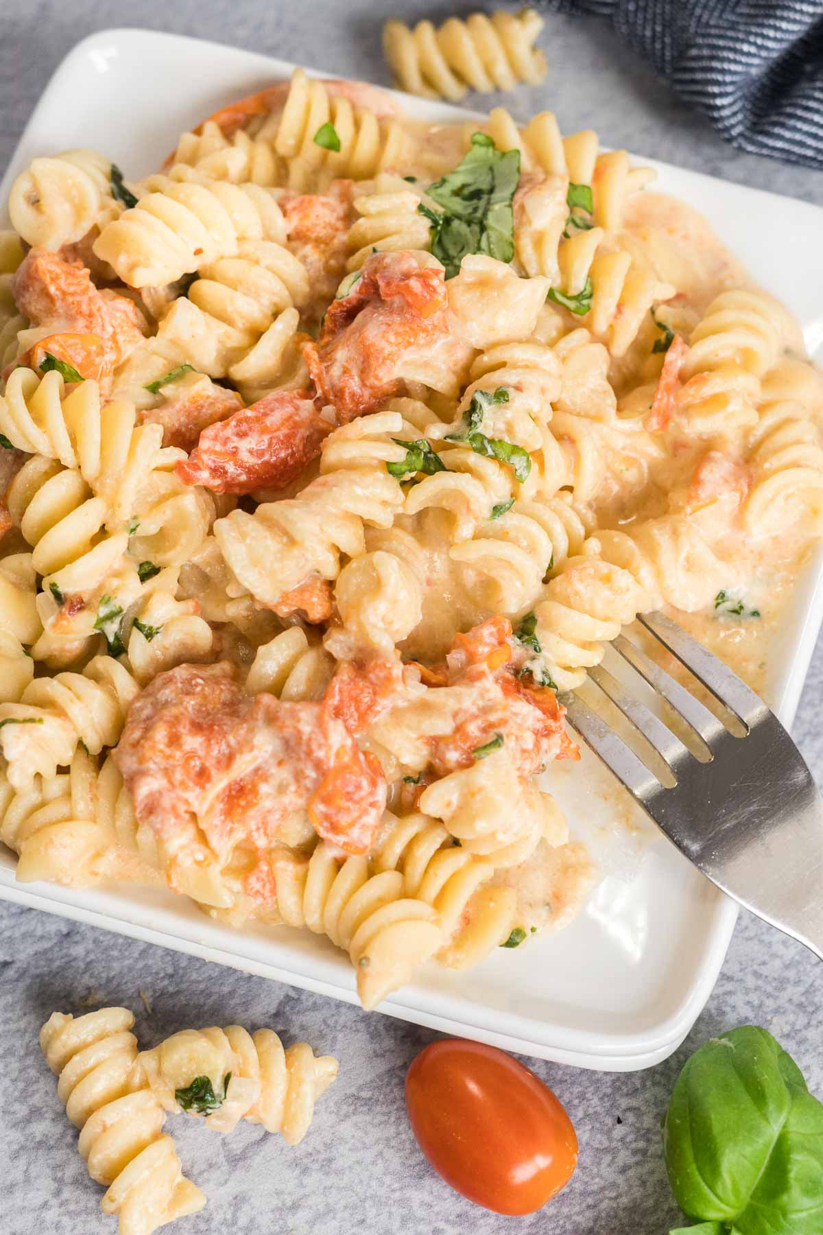 Tomato feta pasta on a white plate with a fork.