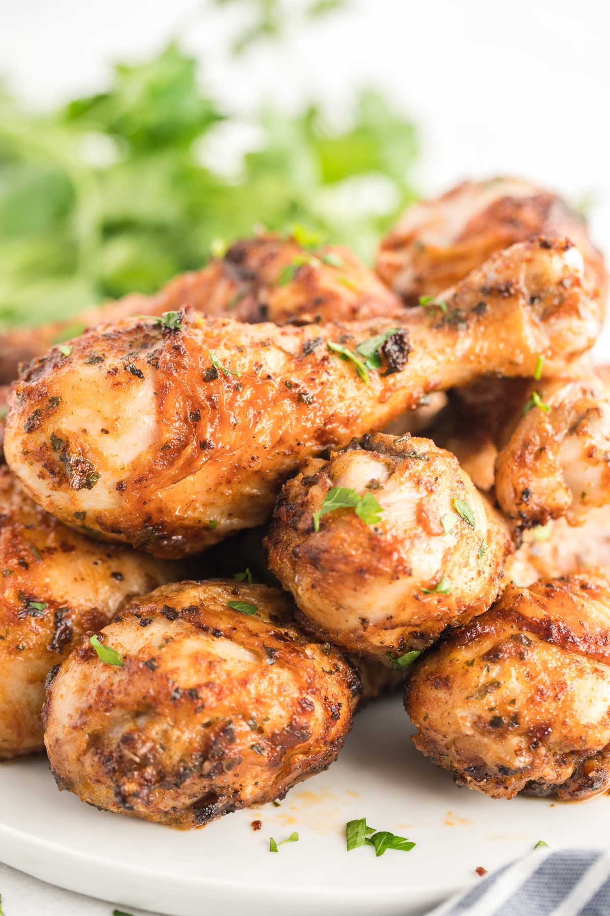 Platter of cooked chicken legs garnished with chopped parsley.