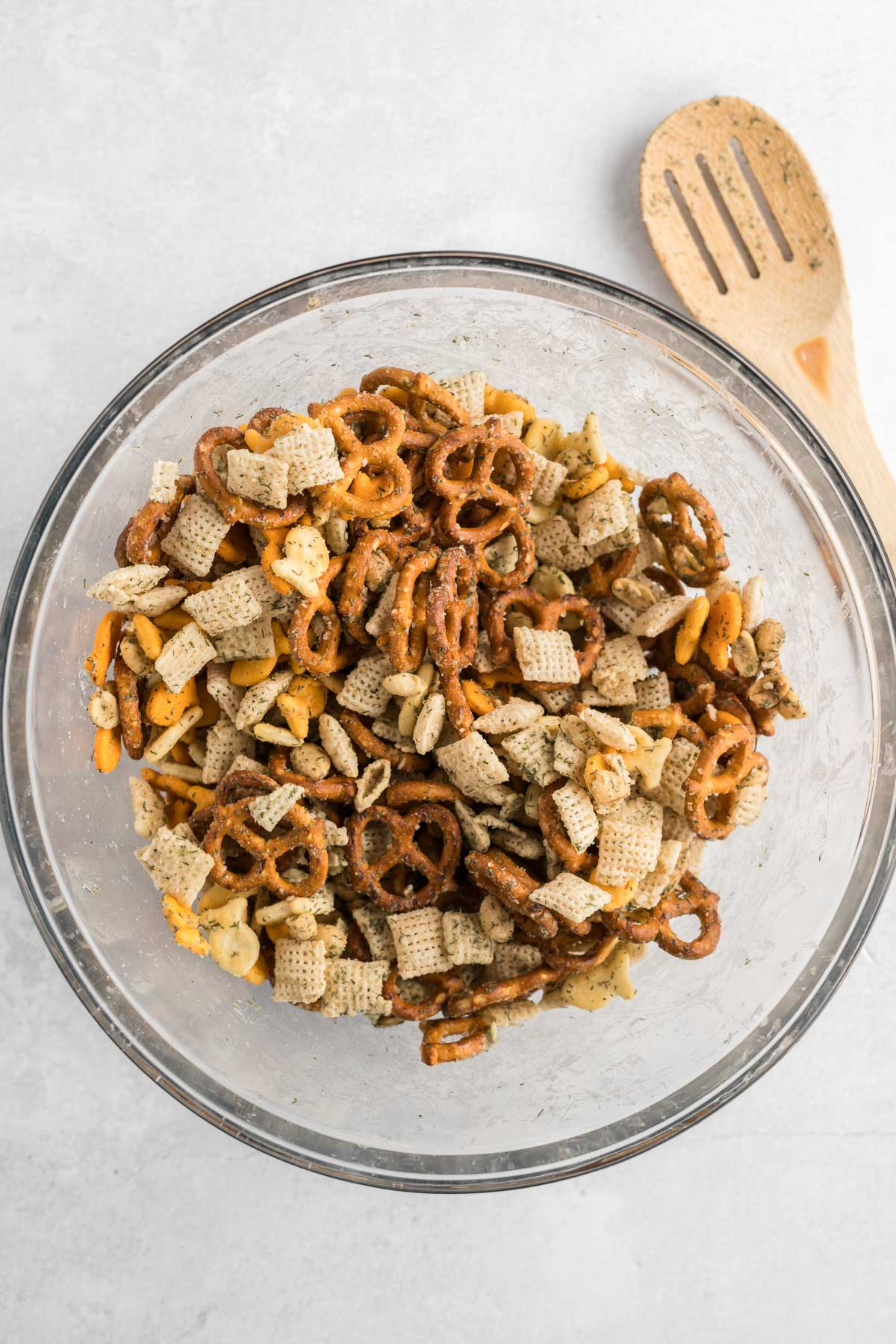 Chex mix, coated in seasoning and mixed in a mixing bowl.