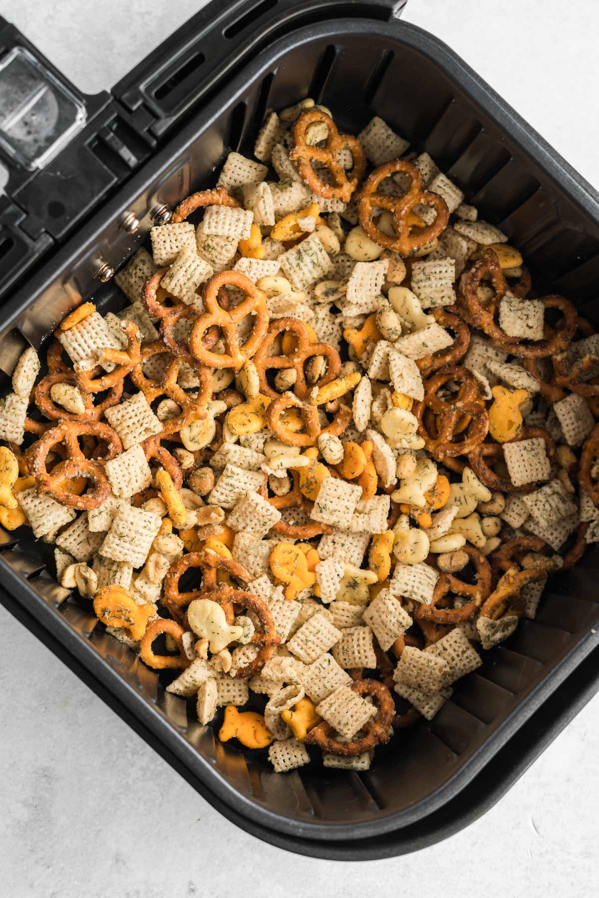 Snack mix in a thin layer in an air fryer basket.