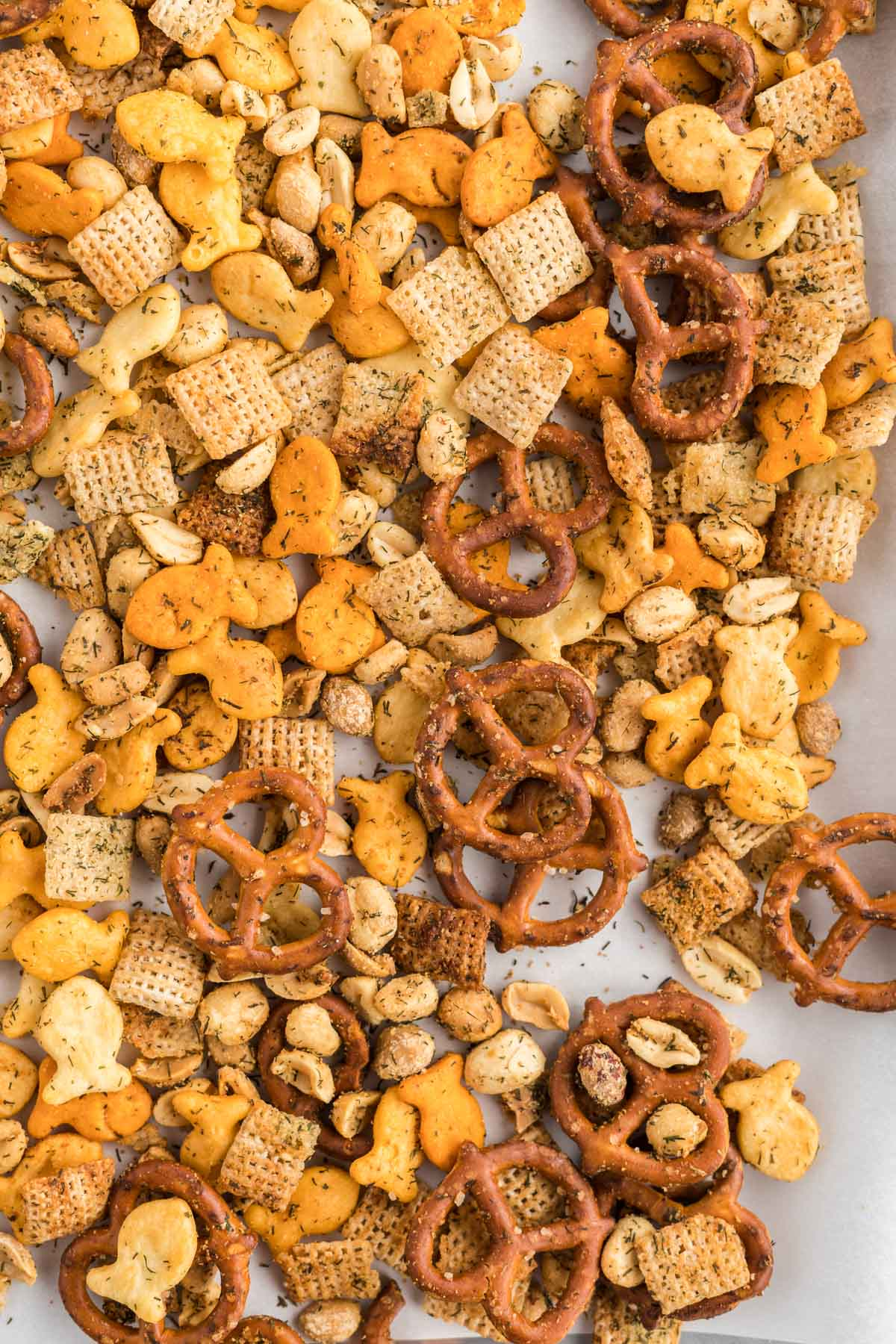 Snack mix of pretzels, goldfish crackers, rice Chex and peanuts on a baking sheet.