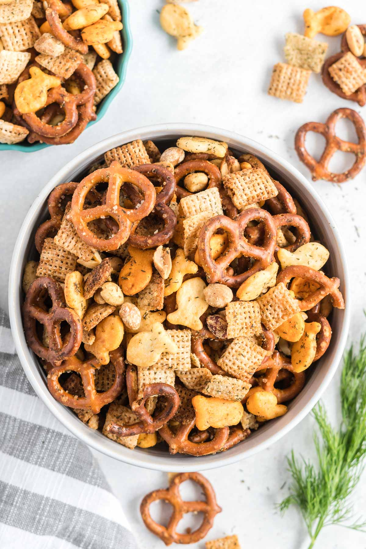 Chex mix in a small bowl with some scattered on the counter.