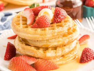 Stack of four cooked waffles with butter, strawberries and maple syrup.