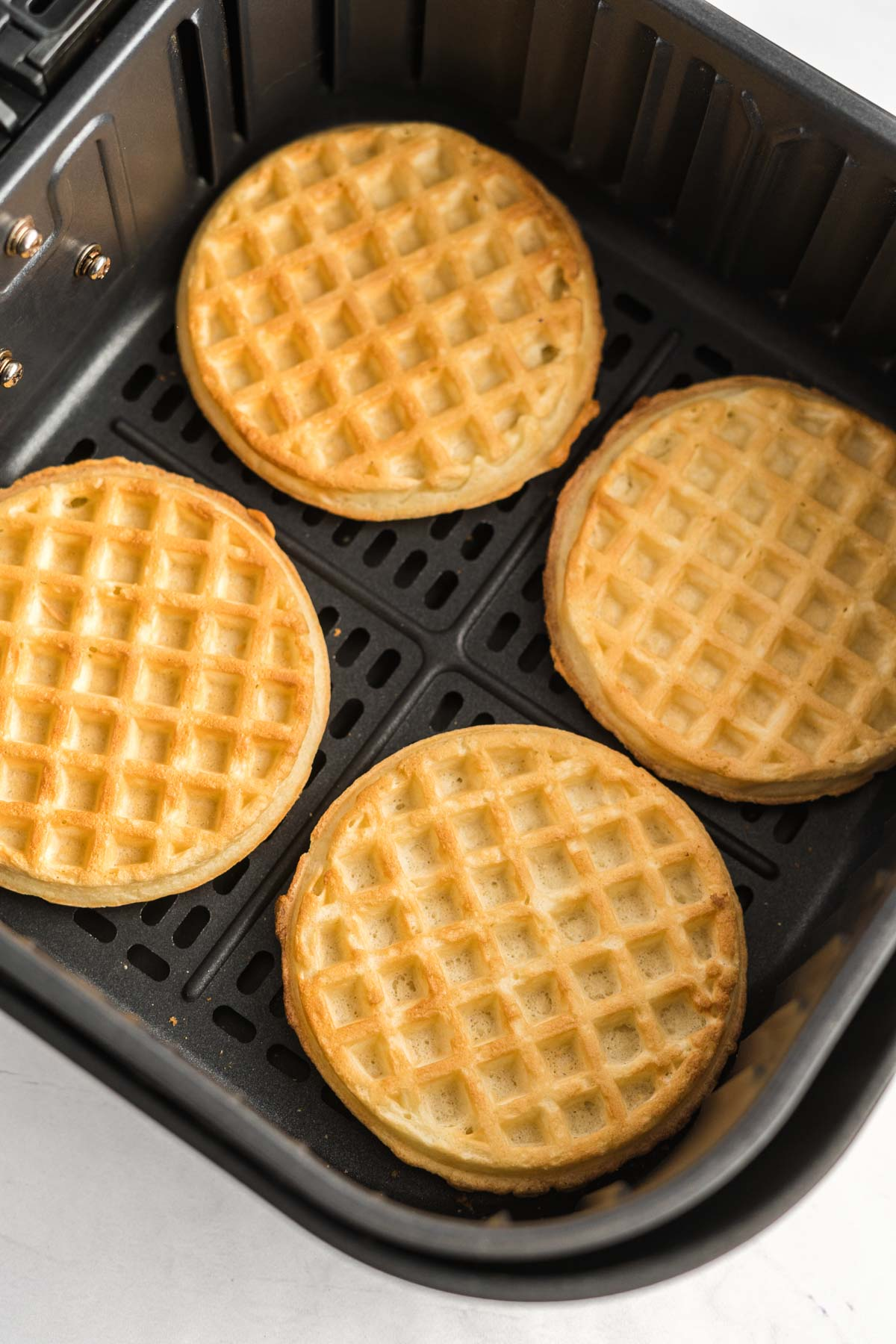 Four frozen waffles in an air fryer basket in a single layer.