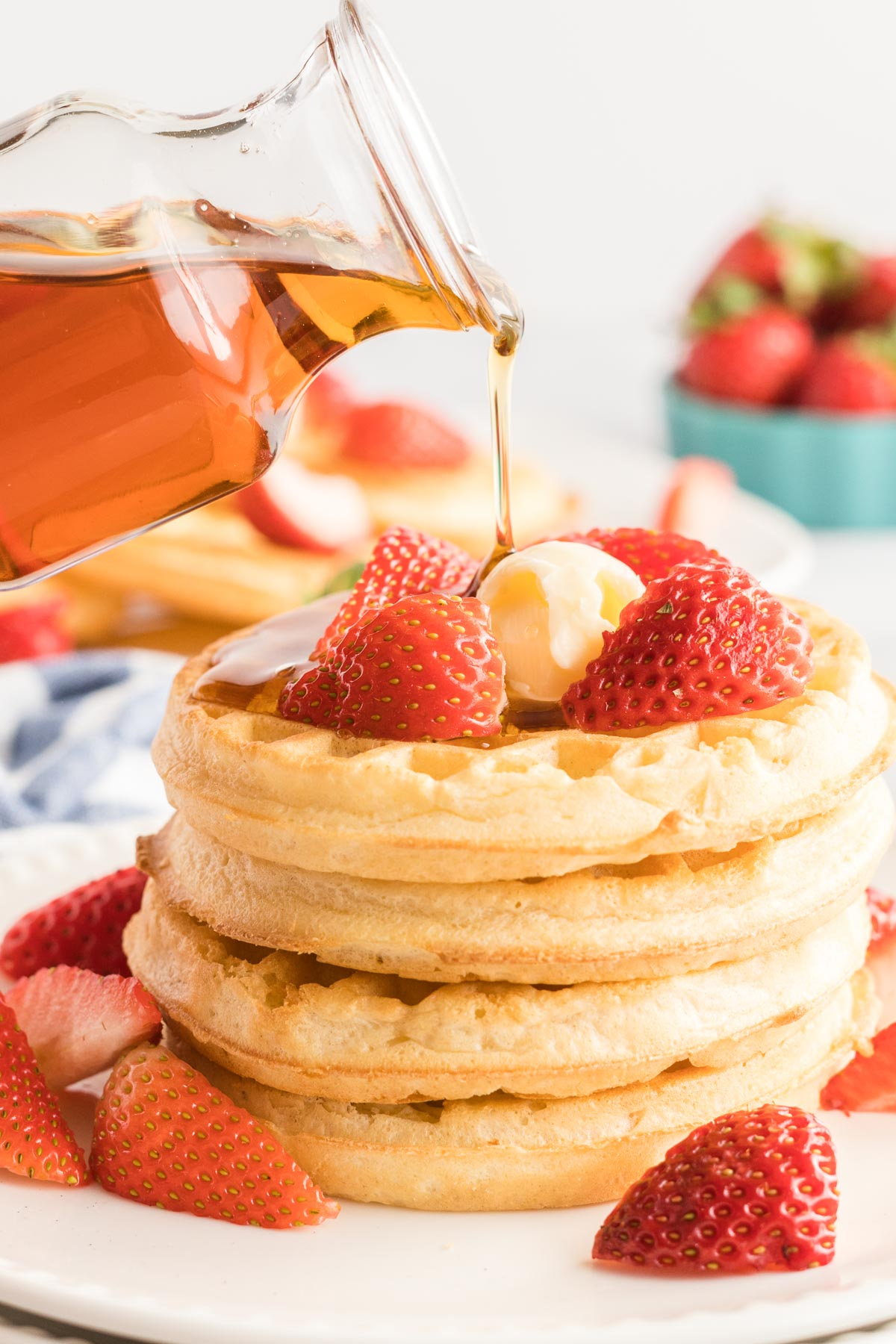 Four waffles in a stack with strawberries a jar of maple syrup being drizzled on top.