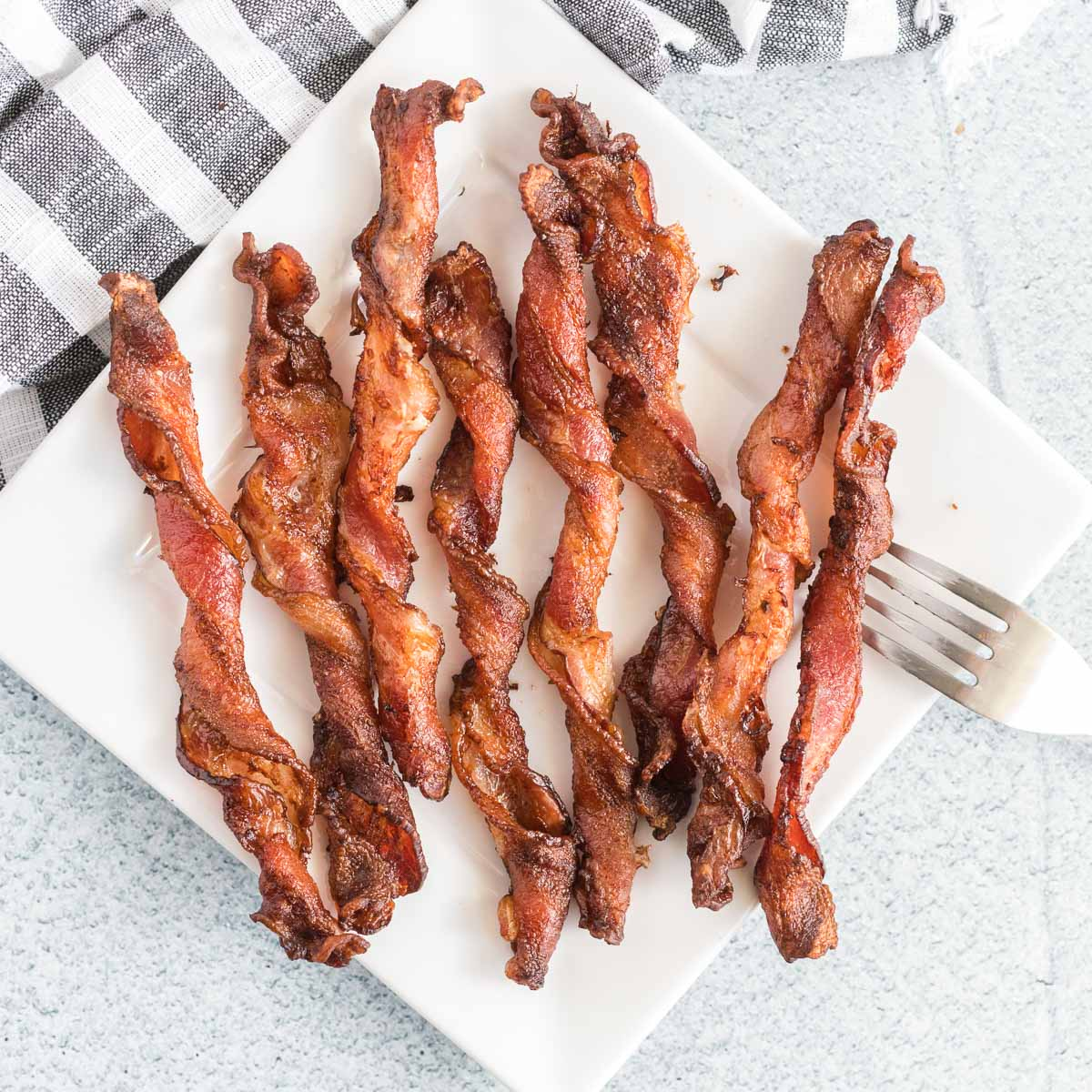 Cooked twisted bacon on a square white plate with a fork.