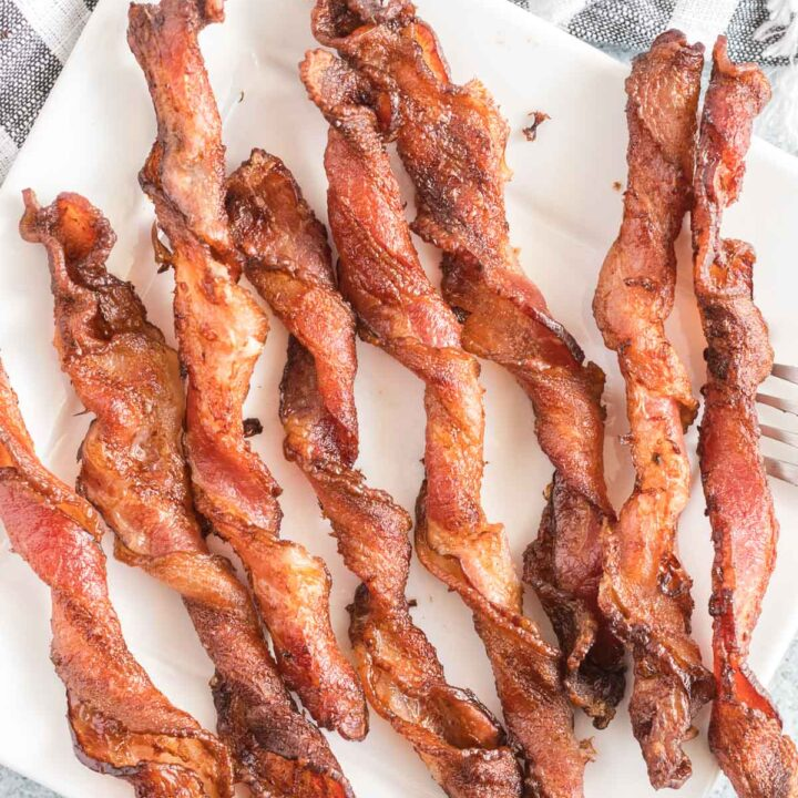 Cooked, twisted bacon on a white plate.