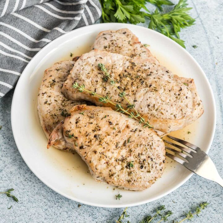 Four cooked pork chops on a white plate garnished with fresh thyme.