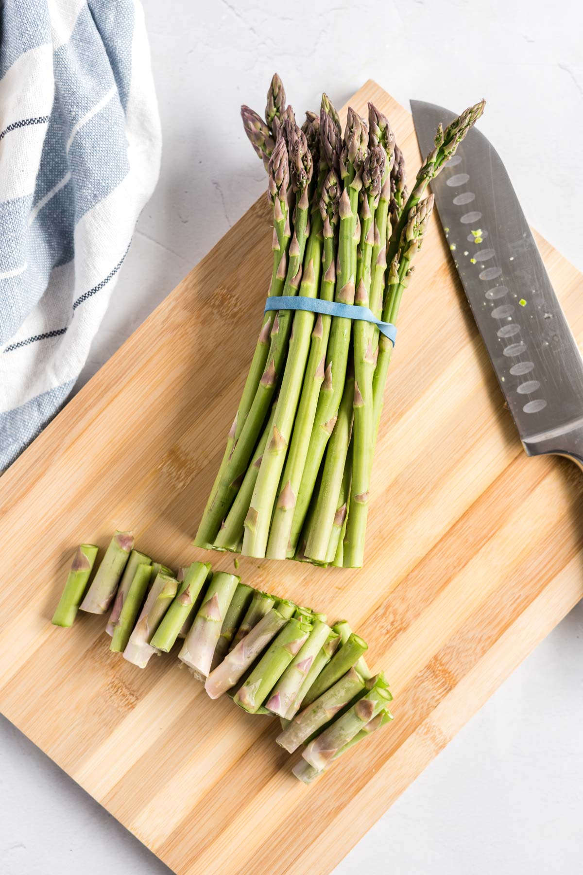Bunch of asparagus in an elastic band on a wooden cutting board with the ends trimmed off.