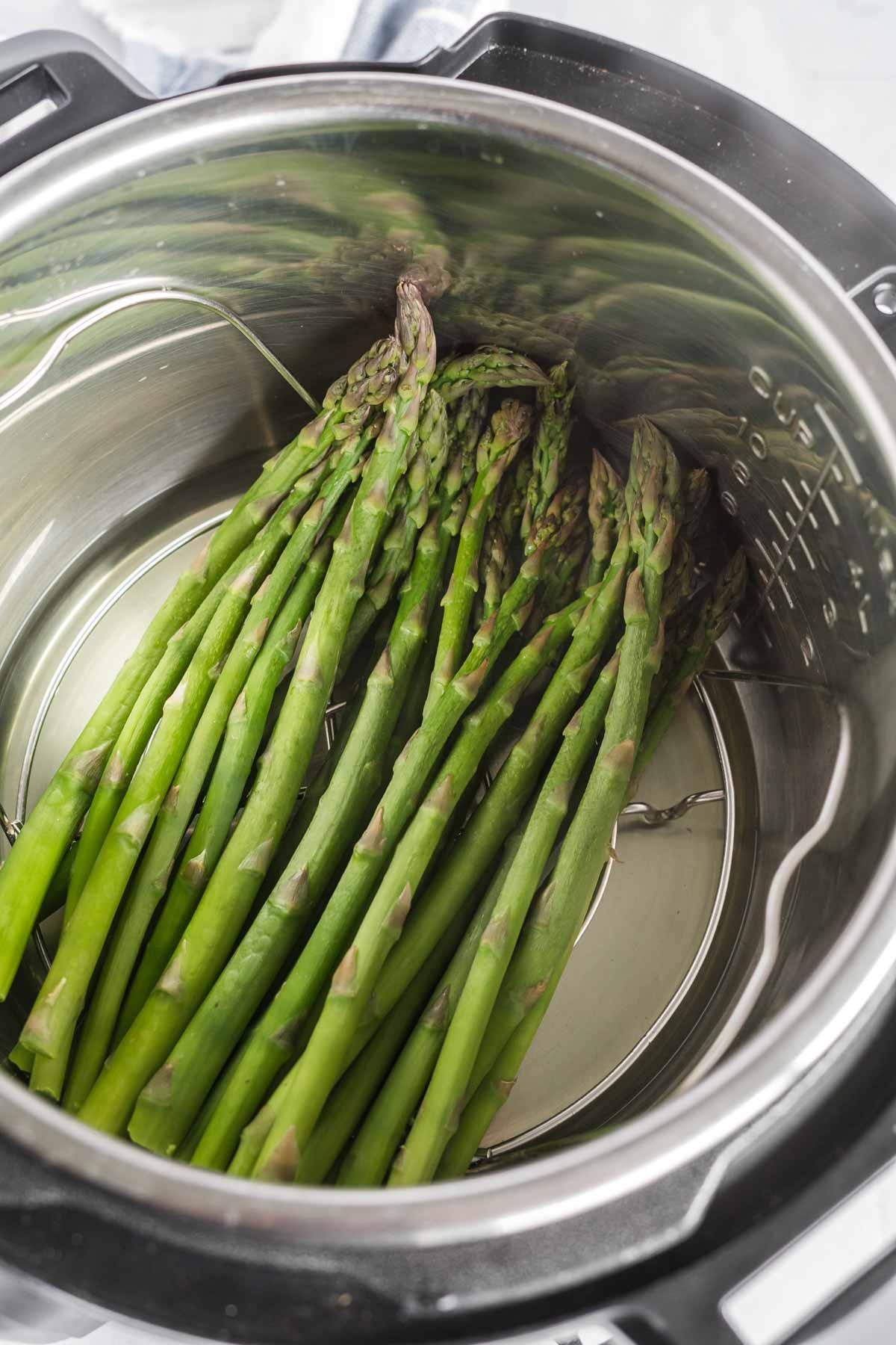 Asparagus on a trivet inside an instant pot.