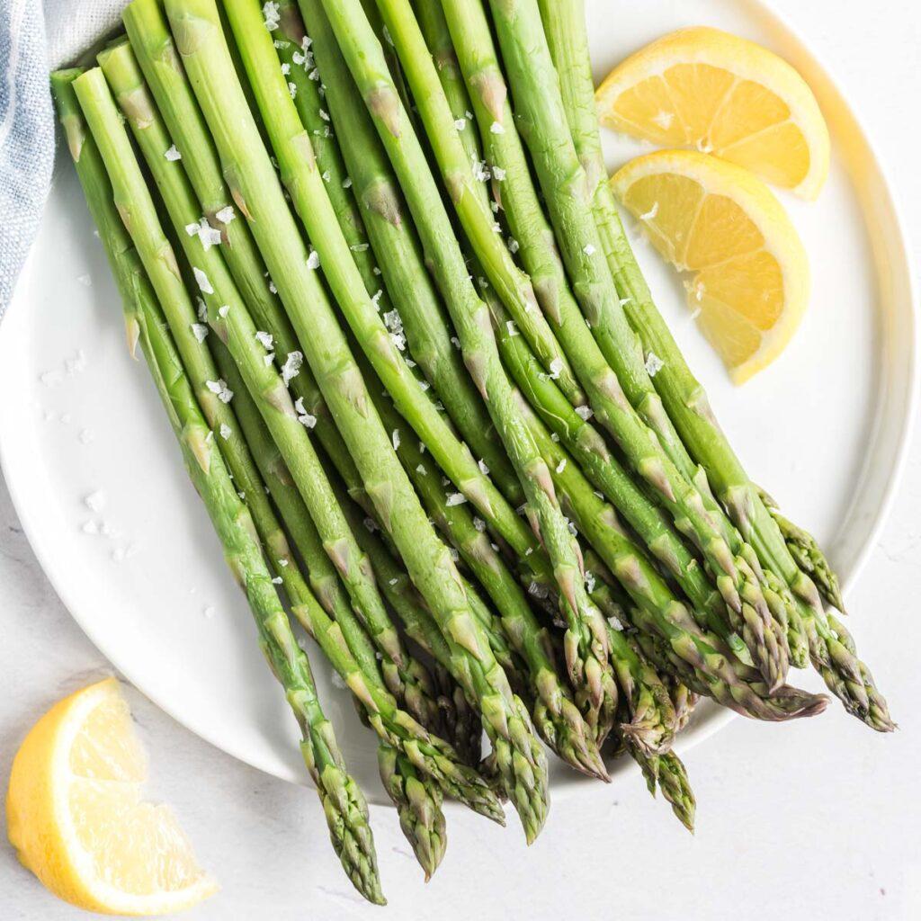 Steamed asparagus on a plate sprinkled with salt and lemon wedges on the side.
