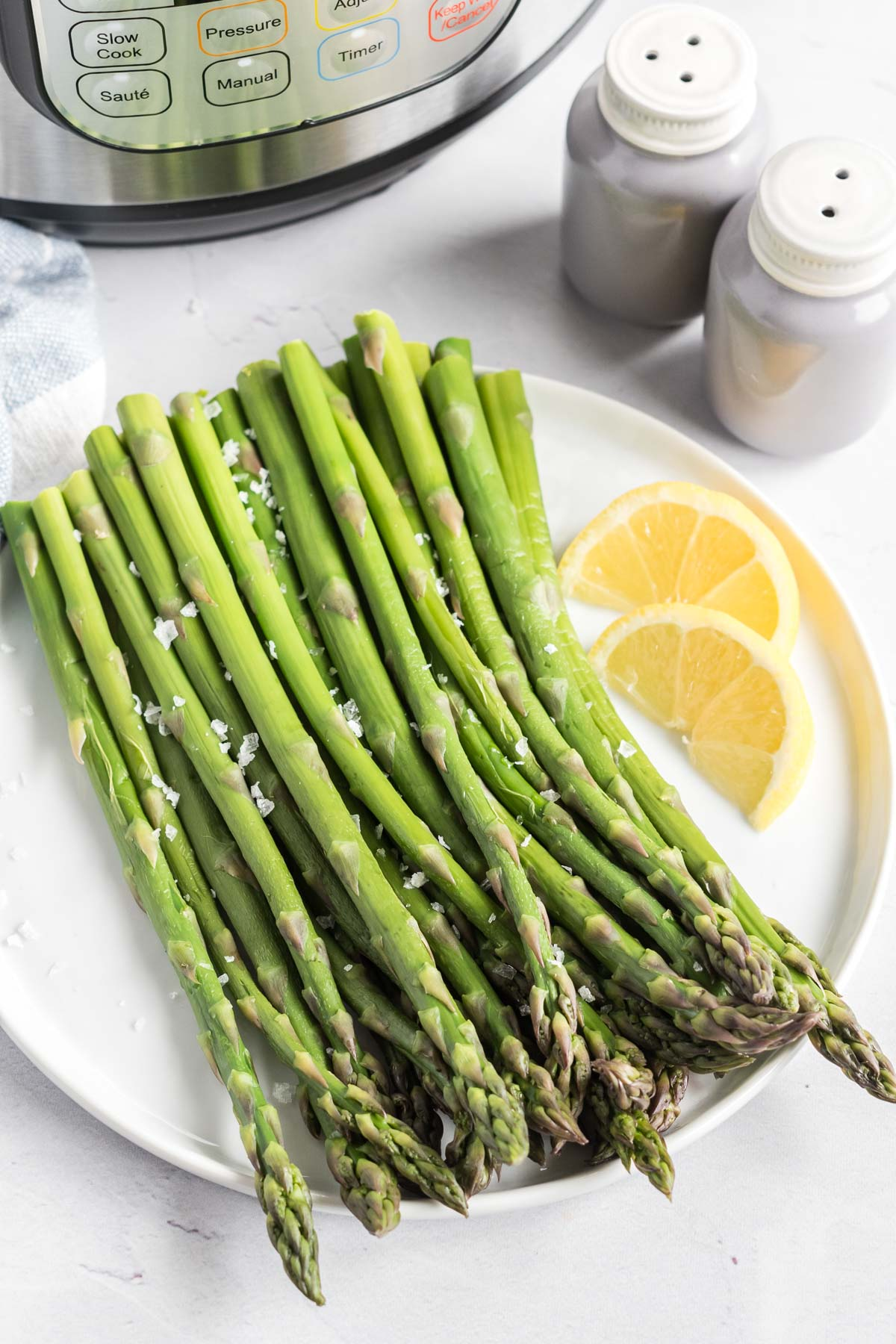 Asparagus on a plate with lemon wedges.  An instant pot and salt and pepper shakers in the background.