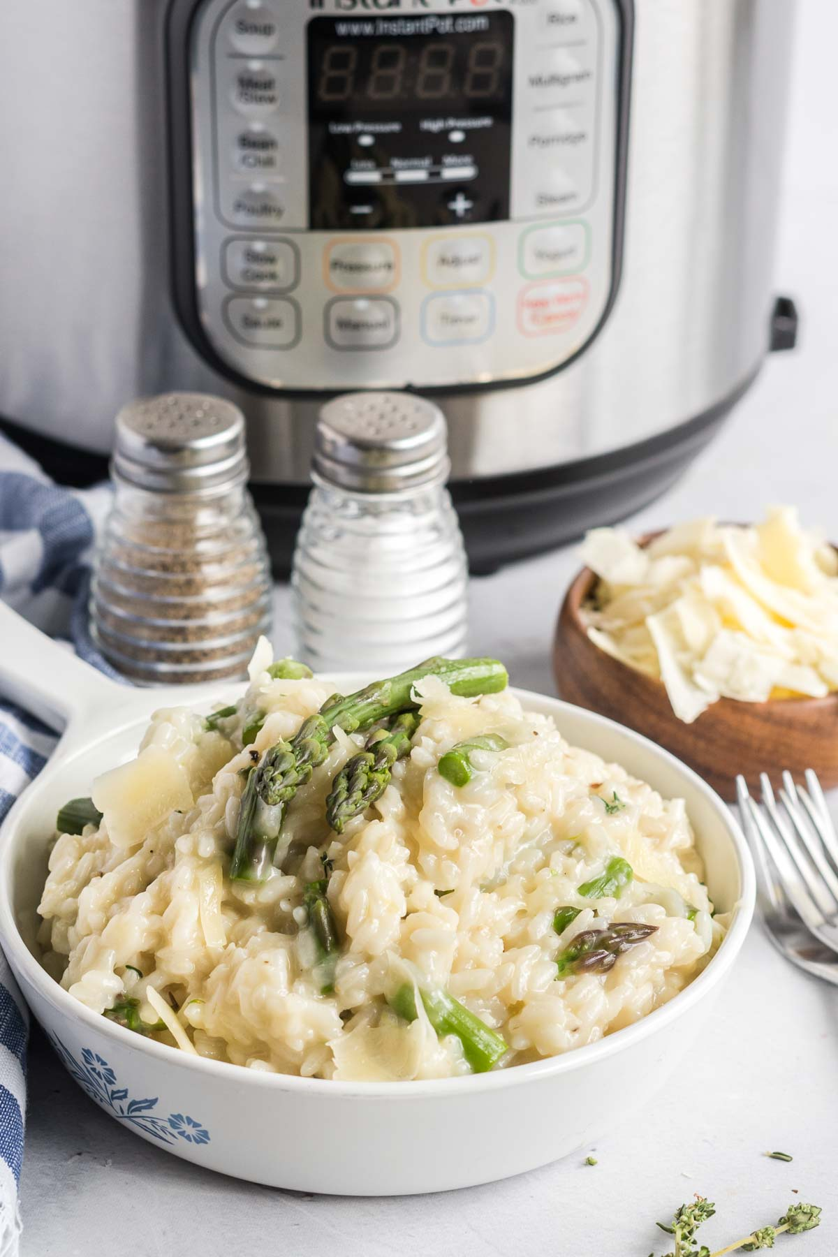 Risotto in a serving dish garnished with parmesan cheese.  Salt and pepper and a small bowl of parmesan on the side.