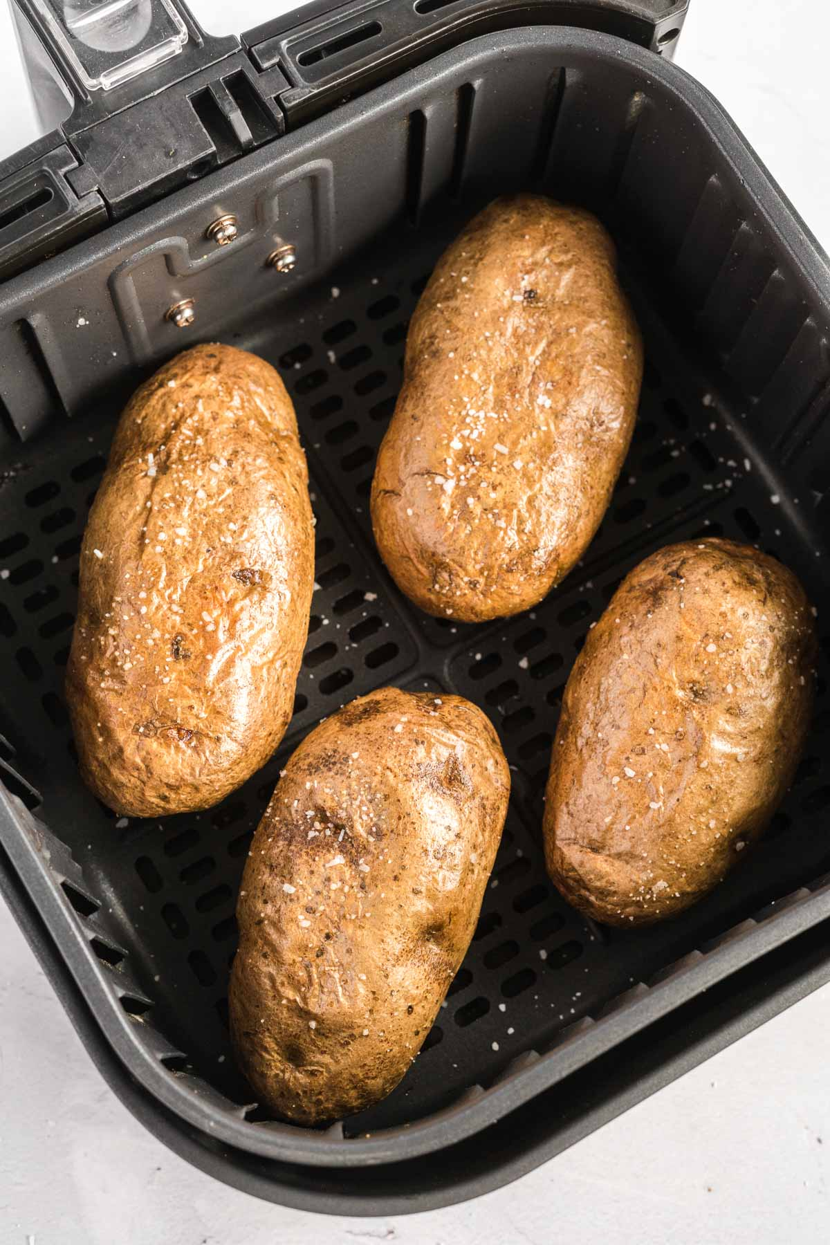 Four baked potatoes in an air fryer basket.