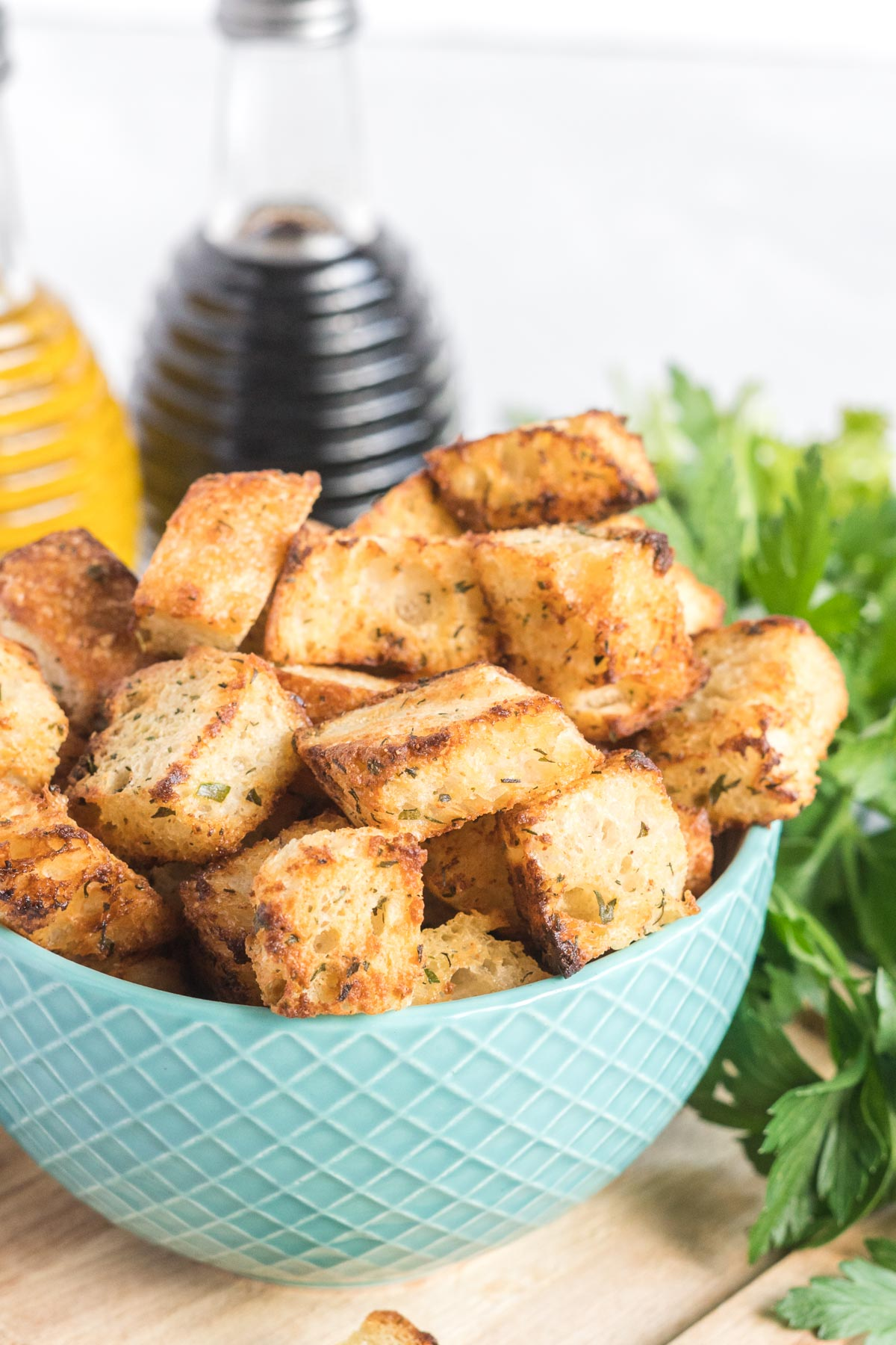 Croutons in a blue ceramic bowl, a bottle of balsamic vinegar and olive oil in the background.