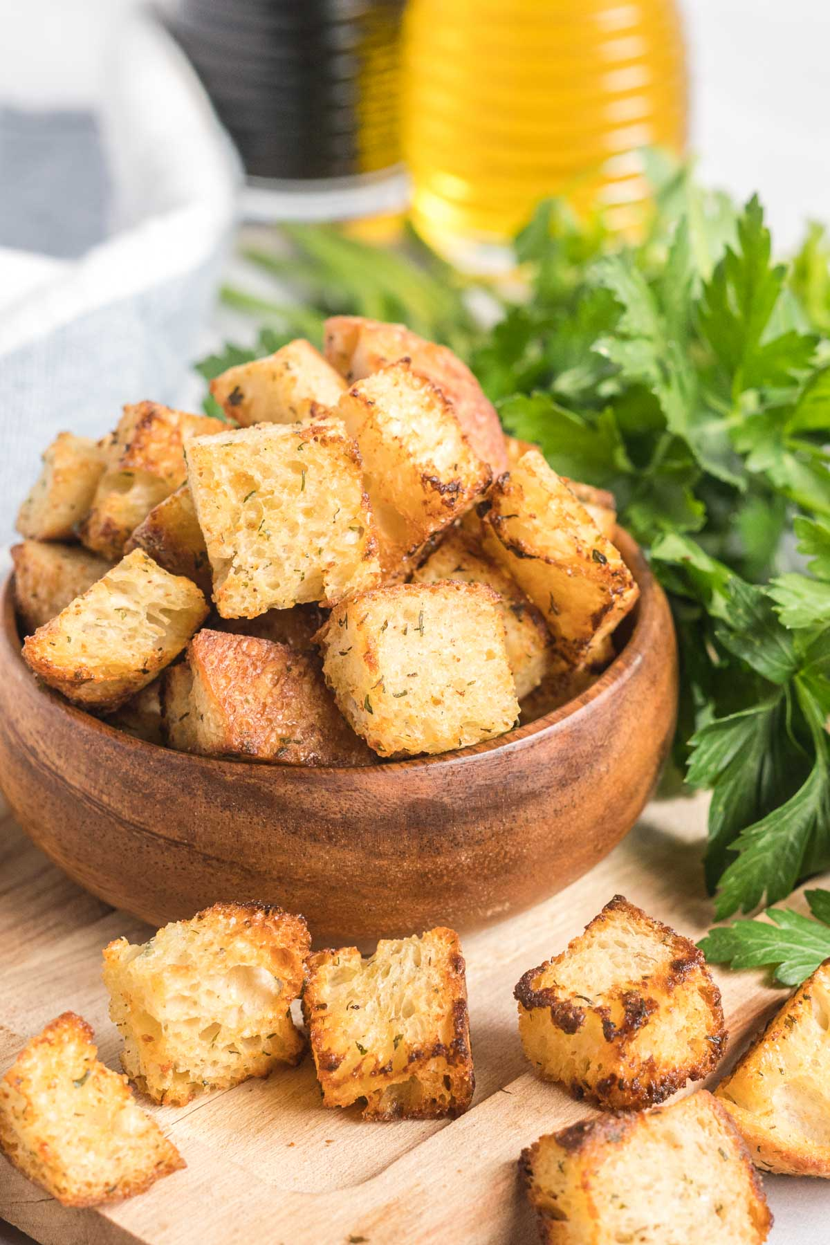 Croutons in a small wooden bowl with a bunch of greens and an oil and vinegar bottle.
