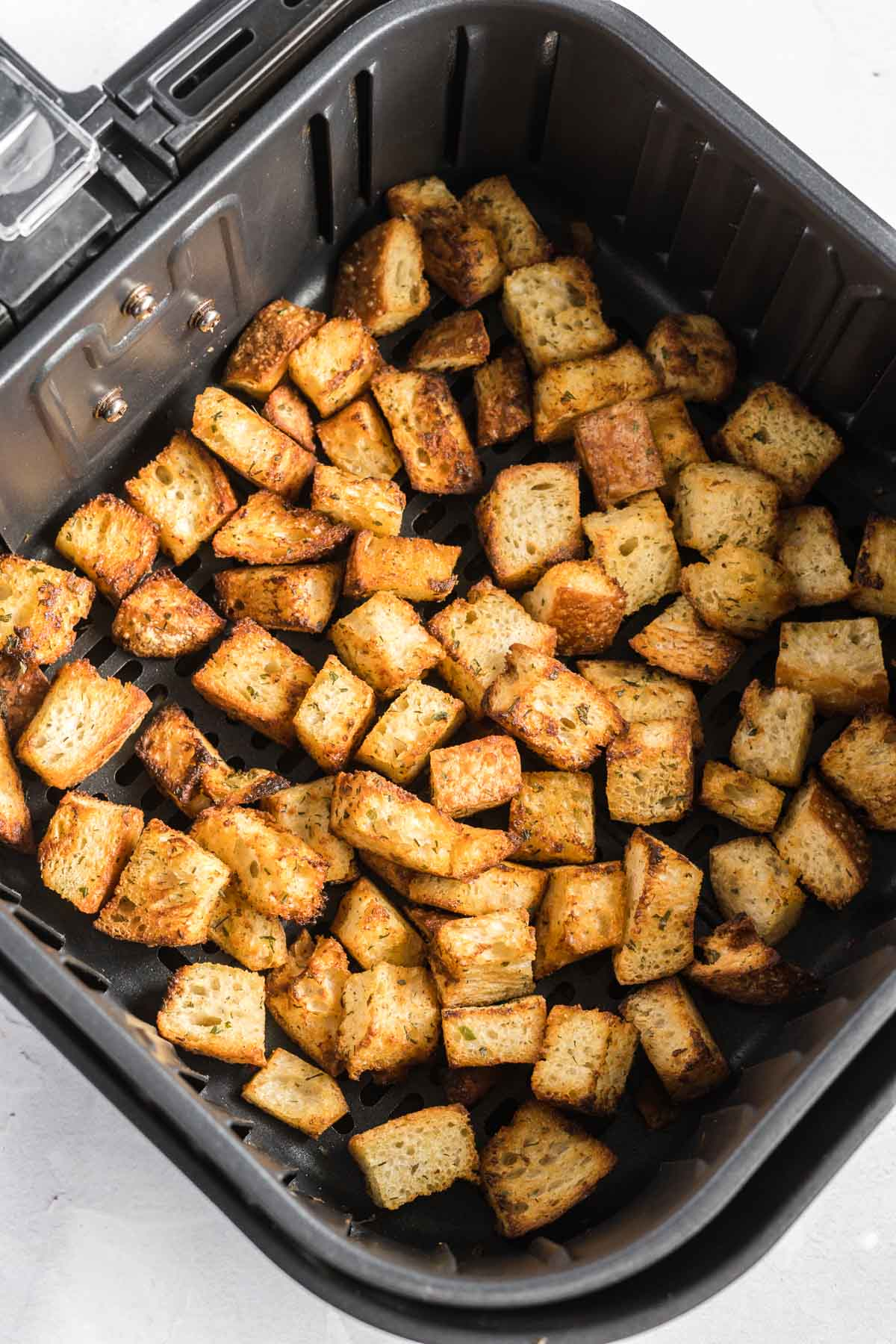 Cooked croutons in an air fryer basket in a single layer.