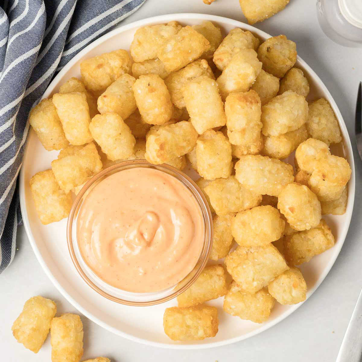 Air fried tater tots on a white plate with a small bowl of spicy mayo.
