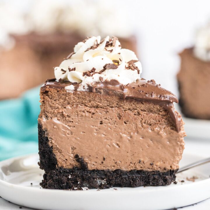 A piece of chocolate cheesecake topped with whipped cream and chocolate shavings on a white plate.