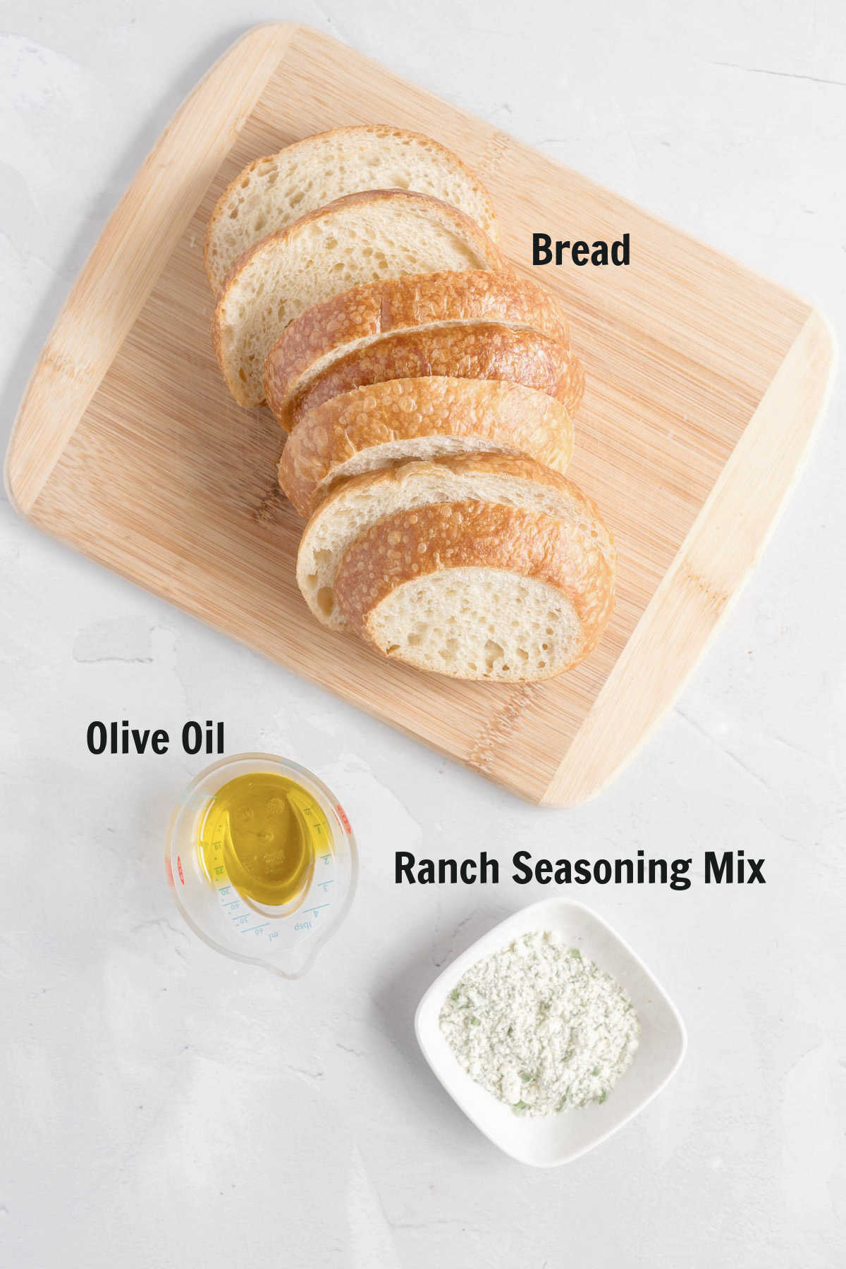 Bread slices on a cutting board, small measuring cup of olive oil and dish of ranch seasoning.