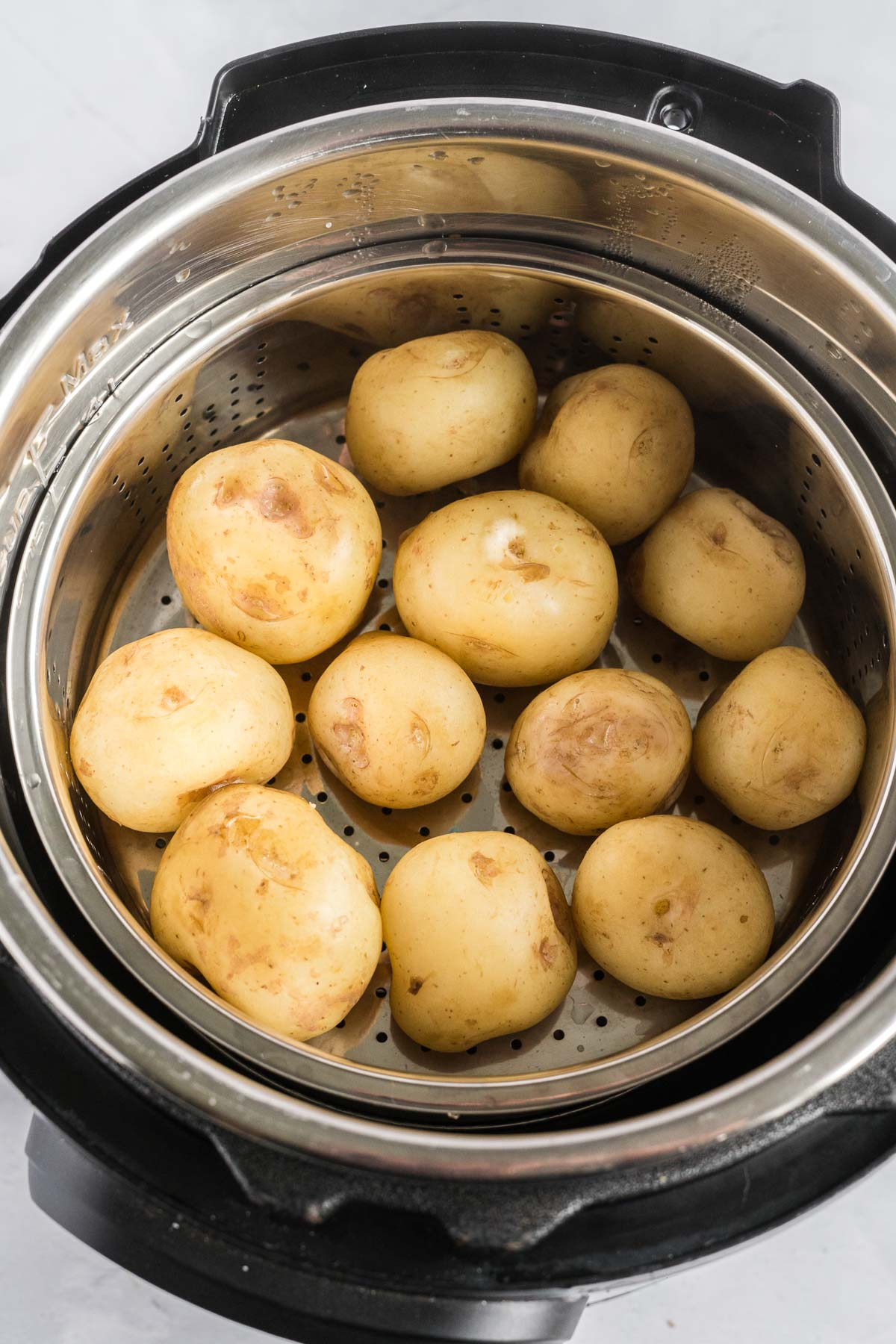 Baby potatoes in a steamer basket inside of an instant pot.