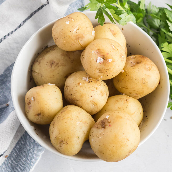 Steamed baby potatoes in a white bowl sprinkled with coarse salt and fresh pepper.