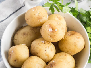 Steamed baby potatoes in a white bowl sprinkled with salt and pepper. A bunch of fresh parsley on the side.
