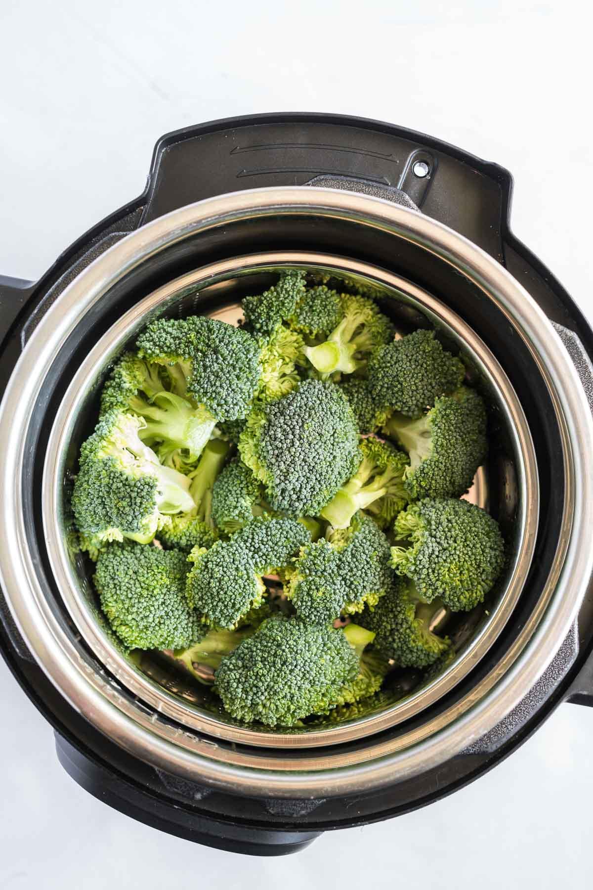Raw broccoli florets in a steamer basket inside an instant pot.