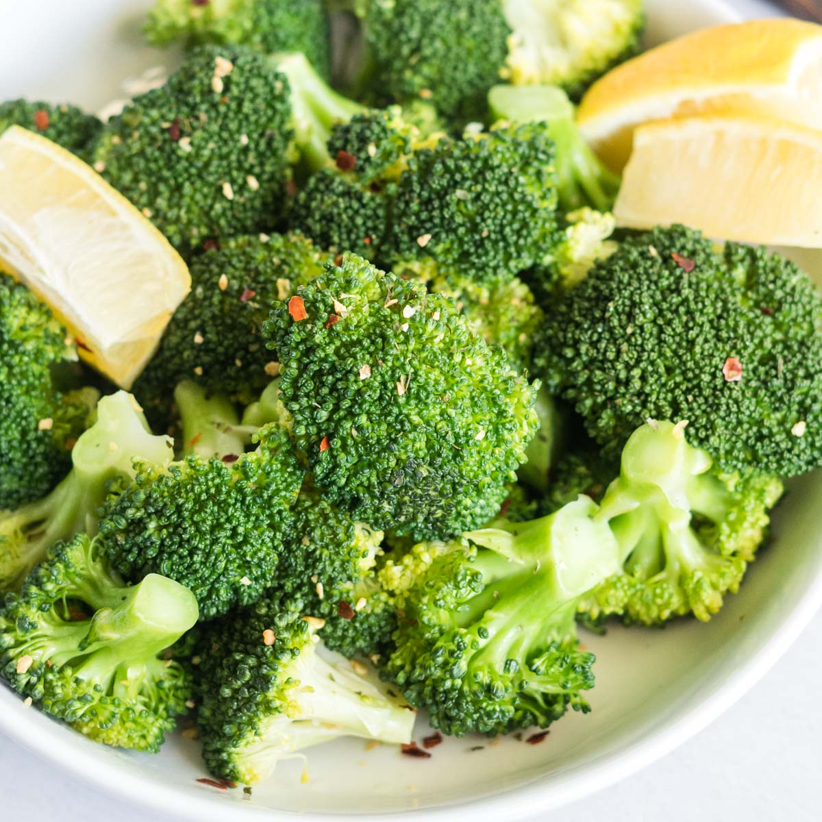 Steamed broccoli in a bowl with lemon wedges and chili flakes.