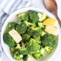 Steamed broccoli in a serving bowl with lemon wedges, sprinkled with chili flakes. A wooden serving spoon on the side.