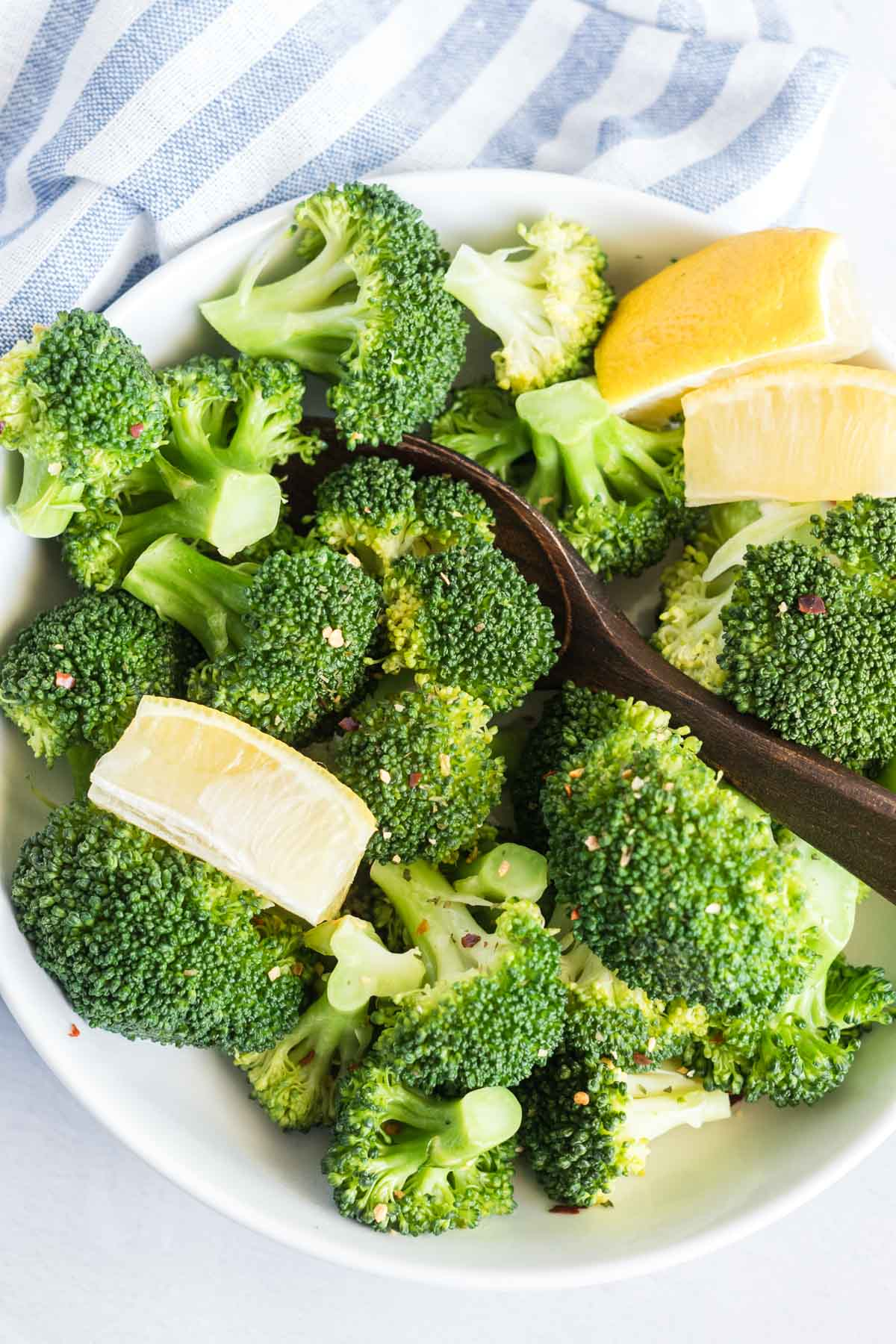 Cooked broccoli in a serving bowl with a wooden spoon.