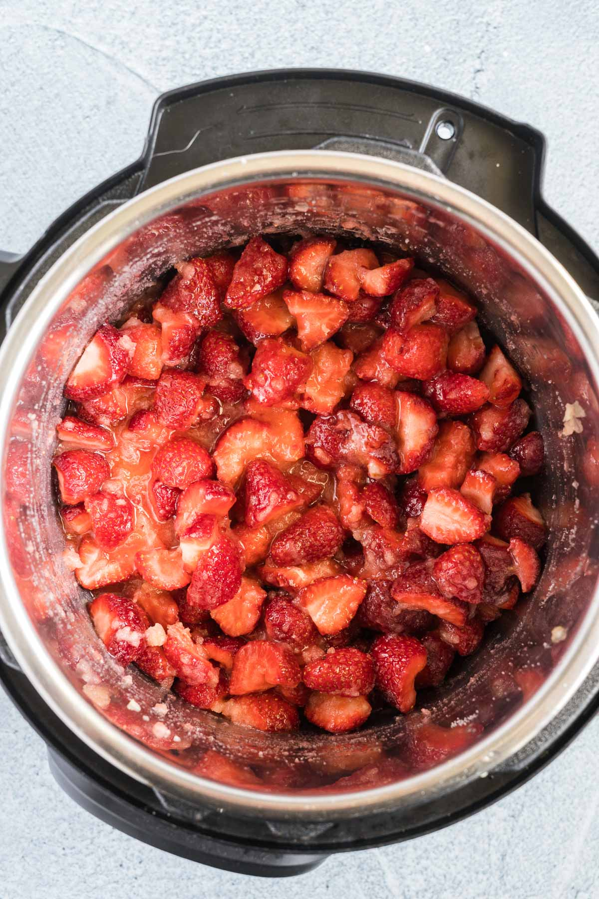 Chopped strawberries mixed with sugar in an instant pot.