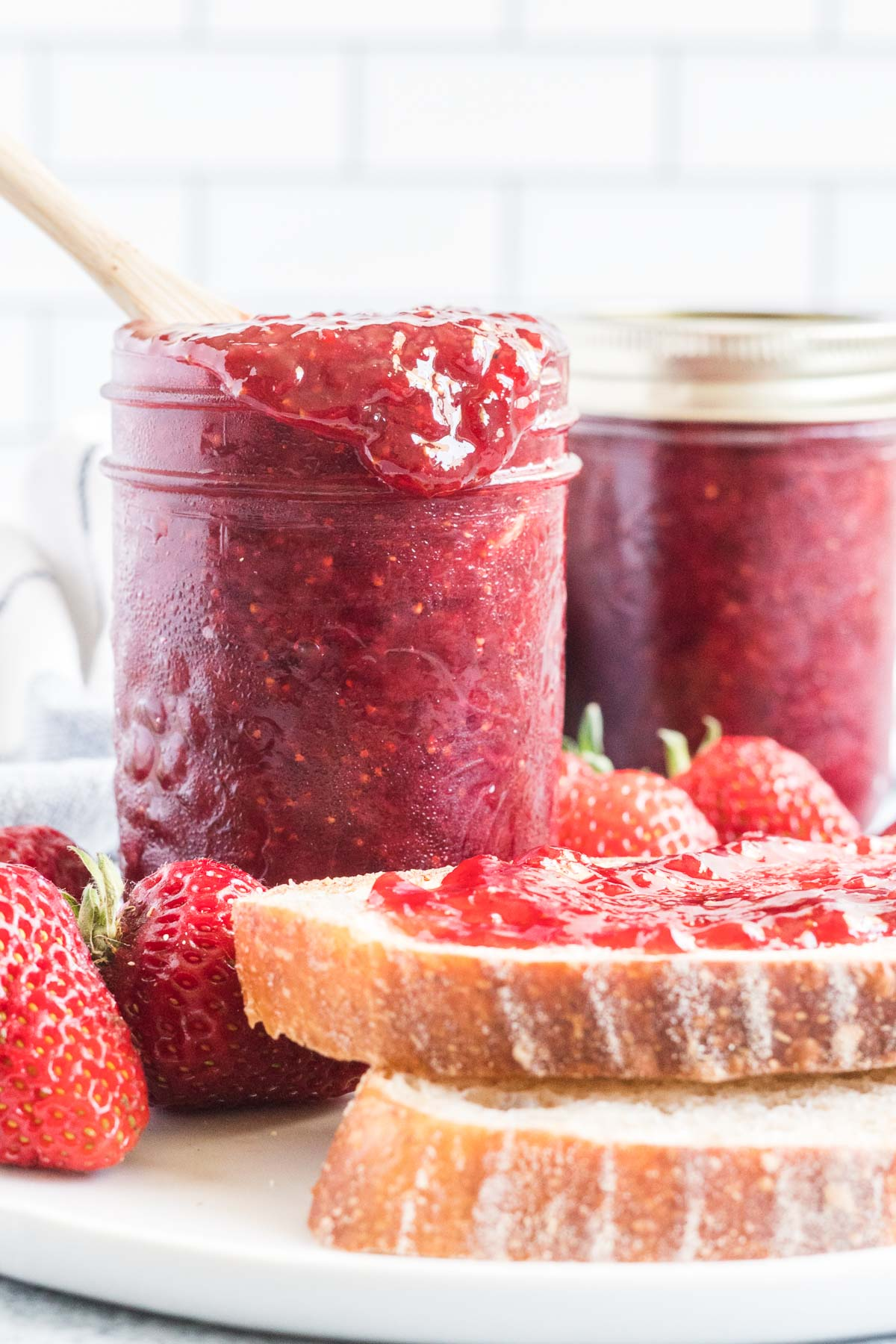A jar of strawberry jam with a spoon and jam dripping over the side of the jar.  Two pieces of toast spread with strawberry jam.
