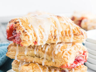 Three cherry turnovers drizzled with icing stacked on a plate.
