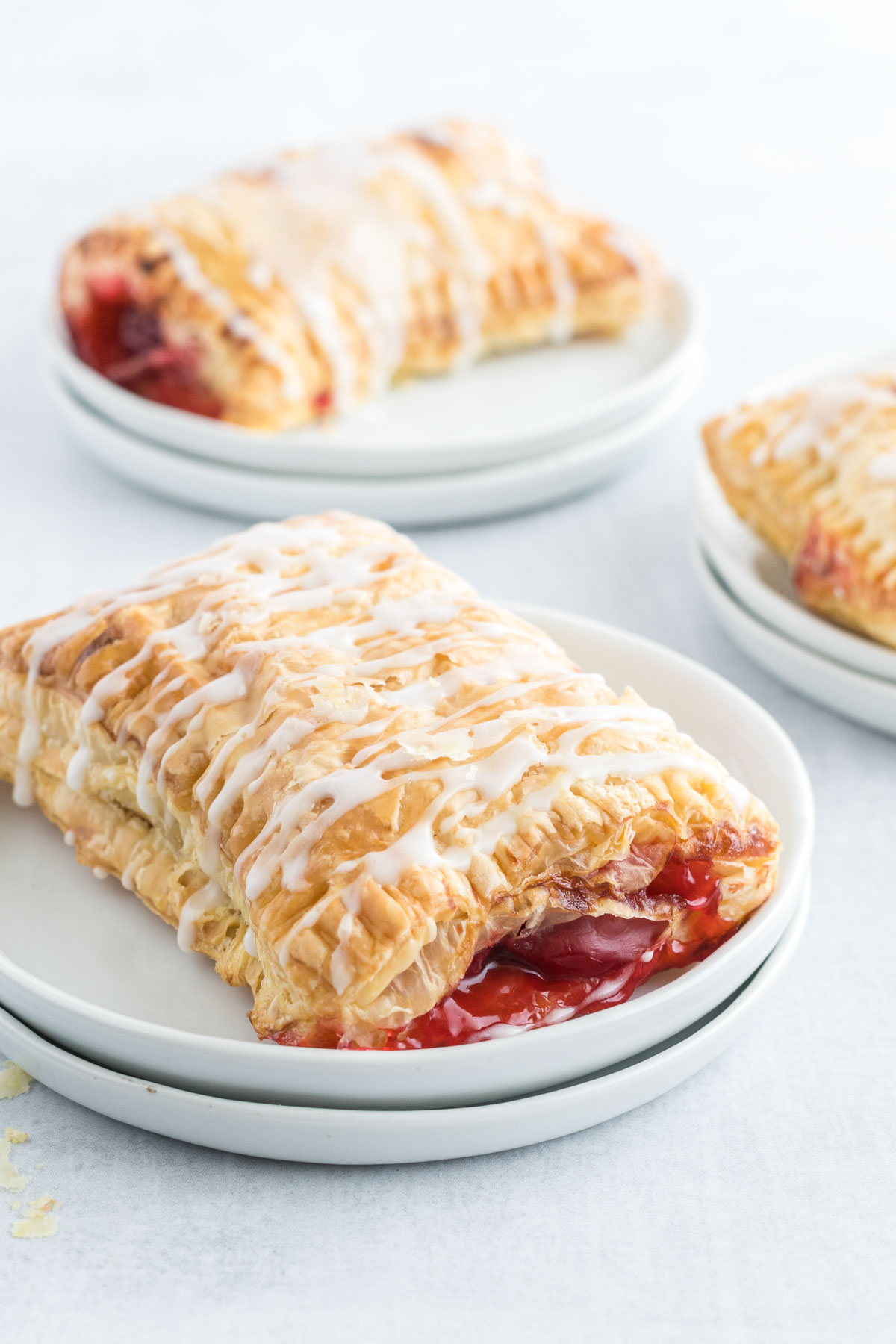 A cherry turnover with icing drizzle on a small plate.