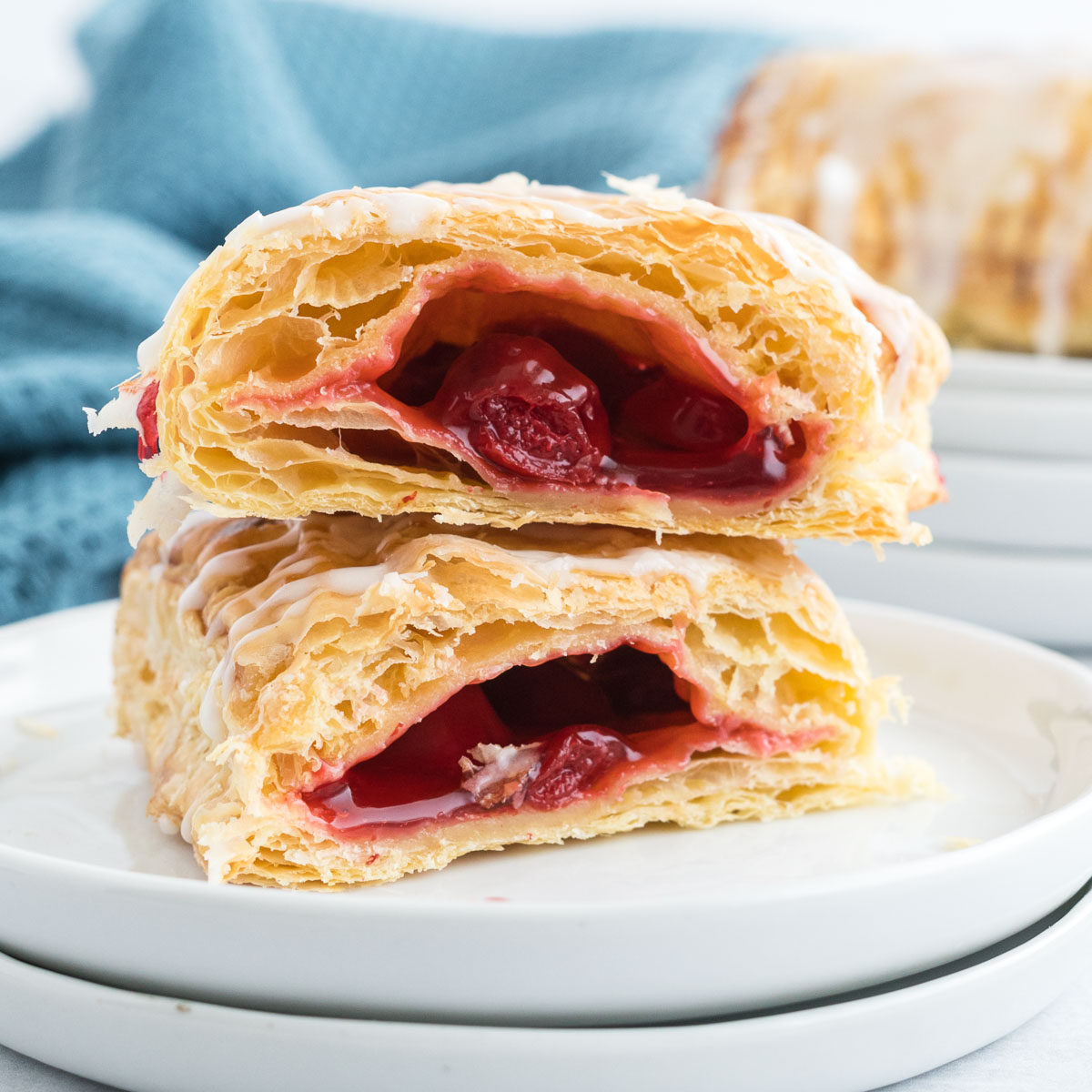 A flaky puff pastry turnover cut in half and filled with cherry pie filling, drizzled with icing.