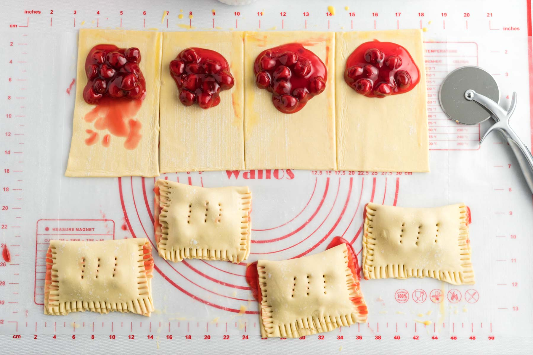 Eight squares of puff pastry with cherry pie filling.  Four squares are folded over the cherry pie filling and the edges crimped with a fork.