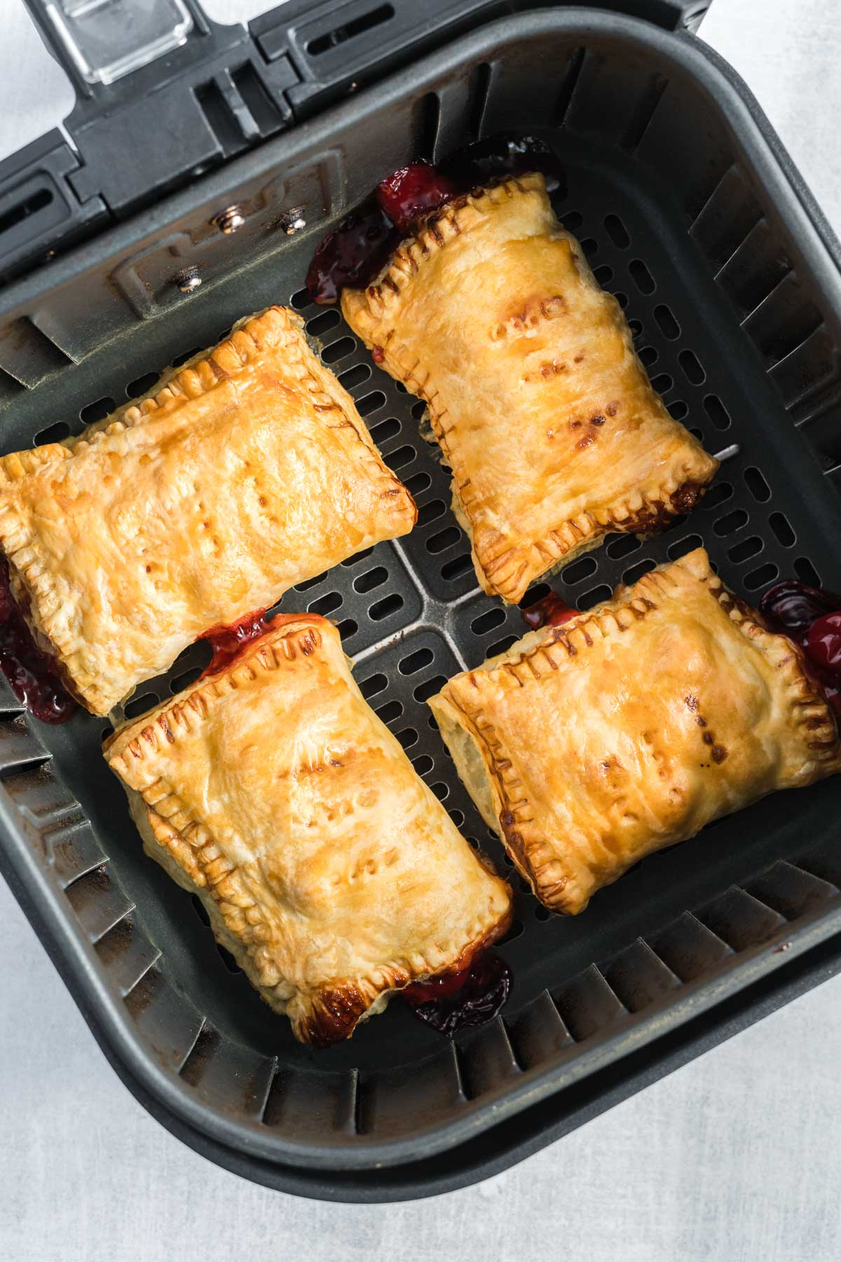 Four turnovers that are puffed and golden brown in an air fryer basket.