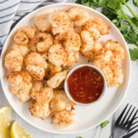 Fried coconut shrimp on a plate with a dish of sweet chili sauce for dipping.